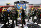 Kyle Busch, driver of the #18 Interstate Batteries Toyota, and his team celebrates in Victory Lane after winning the NASCAR Sprint Cup Series Auto Club 400 at Auto Club Speedway on March 23, 2014 in Fontana, California. - Photo Credit: Jerry Markland/Getty Images