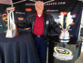 Bobby Allison poses with the NASCAR Sprint Cup Series championship trophy and the Bruton Smith Bank of America 500 trophy in Simpsonville, South Carolina. (Credit: CMS Photo)